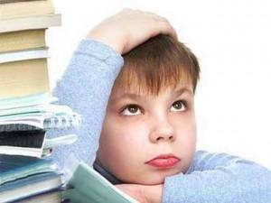 Младший школьник заваленный учебниками